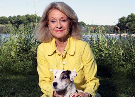 Alexandra Charles i gul kavaj med sin hund