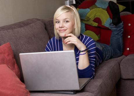 Ung tjej ligger på soffa med datorn framför sig