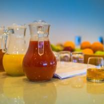Olika juicer i glas och kannor samt fruktkorg