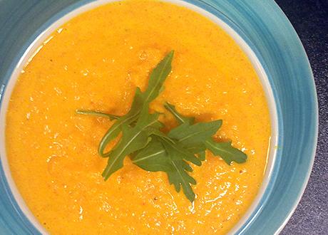 Härligt gul-orange morotssoppa i blå tallrik toppad med ruccola