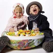 En pojke och en flicka påskklädda med stort påskägg framför sig