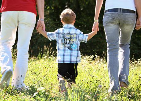 Par går på äng med liten kille mellan sig håller händerna