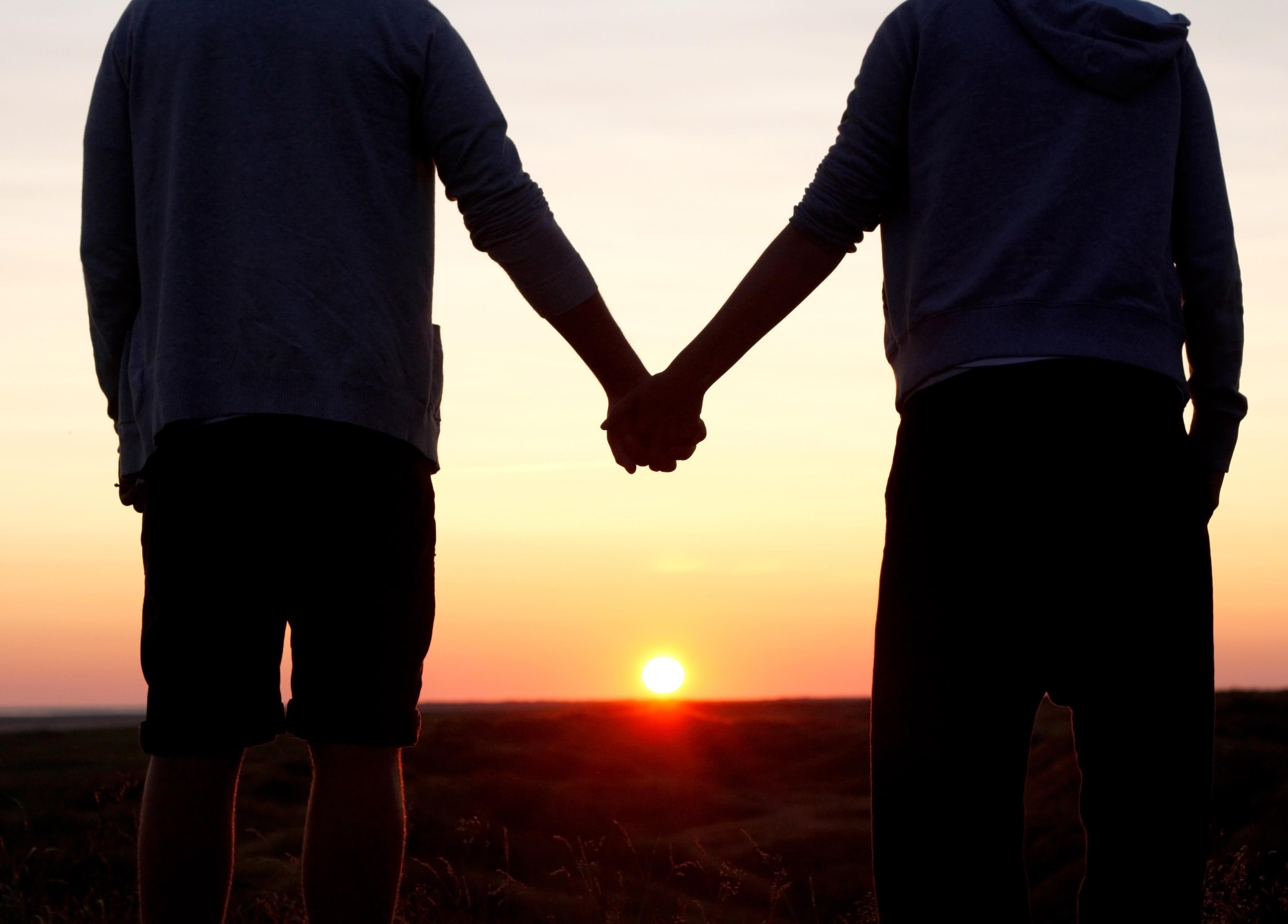 Par håller handen i solnedgång
