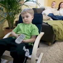 Sjuårig pojke sitter med en tv-dosa och tittar stumt rakt fram