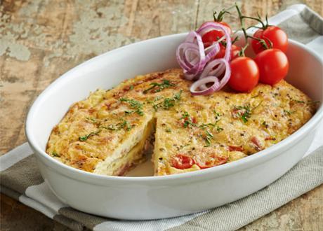 Omelett i ugnsform serverad med coctailtomater på kvist och rödlök