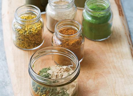 Glasburkar med olika superfoods i pulverform
