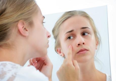 Ung kvinna tittar på sin hy i spegel