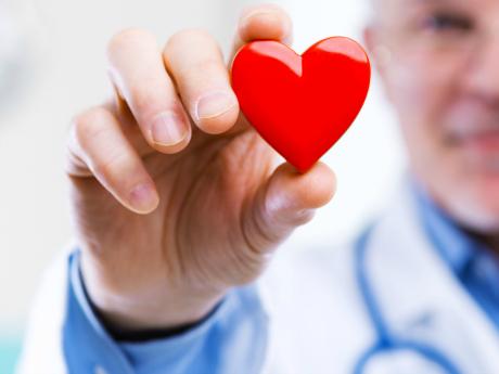 man med läkarrock och stetoskop håller upp rött hjärta