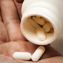 Hand häller ut tabletter i andra handen