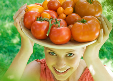 Kvinna med korg tomater på sitt huvud