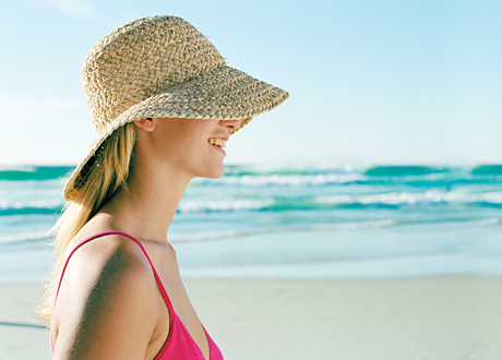 Tjej i solhatt vid strand