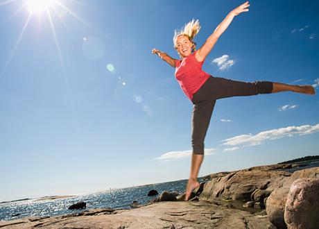 tjej hoppar på bergshäll i solsken