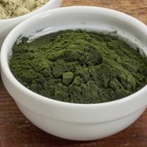 Vit skål med grönt spirulinapulver
