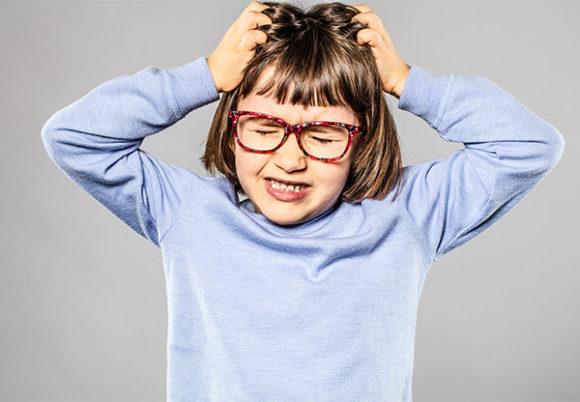 Irriterad ung flicka med glasögon som kliar sig i håret på grund av löss