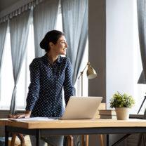 Glad kvinna vid höj- och sänkbart skrivbord som blickar ut