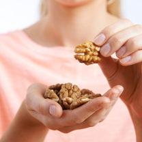 kvinna som håller en näver med valnötter