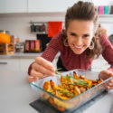 Kvinna lagar vegomat i ugnsfast form