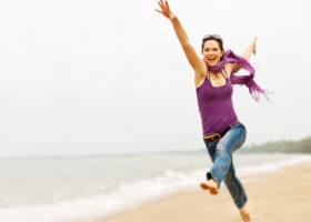 Energifylld glad kvinna på strand