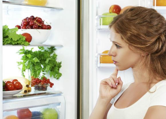 kvinna funderar på vad som finns i kylskåpet
