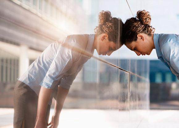 Kvinna lutar huvud mot glasvägg - hennes spegelbild syns i väggen