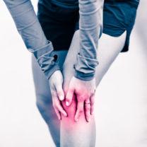 Kvinna håller sig om sitt ben som om smärta