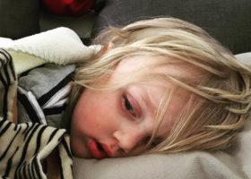 Liten febrig treårig pojke ligger mot kudde