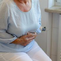 Äldre kvinna håller sig om magen som om smärta