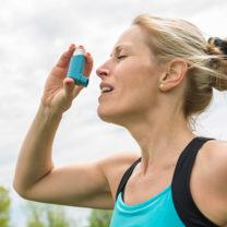 Kvinnlig löpare tar astmaspray