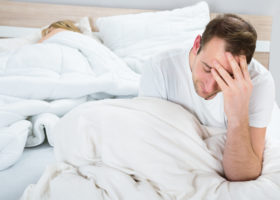 Deppig man sitter i sängen med huvudet i handen