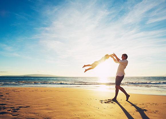 Man svingar sitt barn i armarna på vacker strand