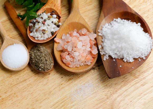 Olika sorters salt på träskedar på träbord