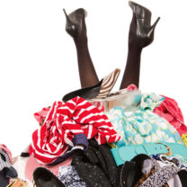 Kvinnofötter i högklackat sticker upp ur klädberg