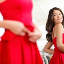 Tjej i röd klänning speglar sig
