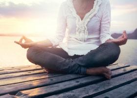 kvinna utövar mindfulness på brygga