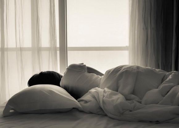 tjej ligger på säng i mörkt rum