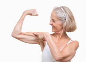 Äldre kvinna spänner sin biceps