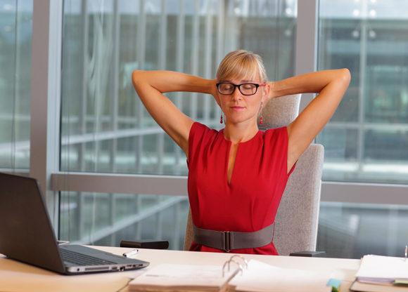Kvinna sitter i avslappnad position på sitt kontor