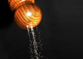 Salt kommer ur ett uppochnedvänt saltkar mot svart bakgrund