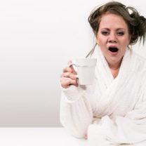Trött kvinna i vit morgonrock gäspar med sin kaffe i handen