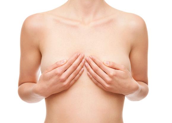 Kvinna håller sina händer över sina bröst