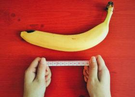 person med måttstock mäter banan