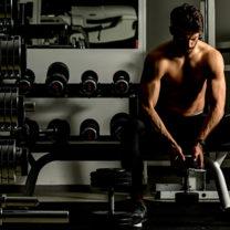 Muskulös man med bar överkropp sitter i gym