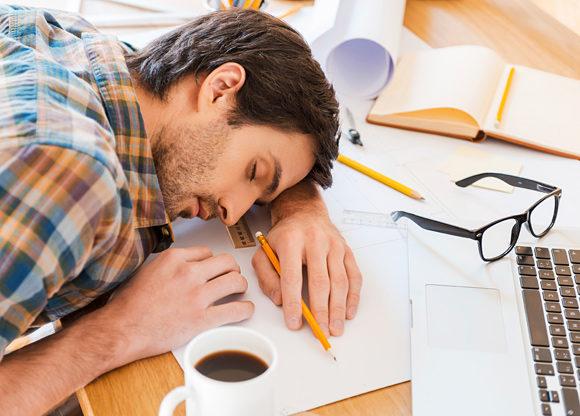 Kille sover med huvudet på sitt skrivbord intill laptop och kaffekopp