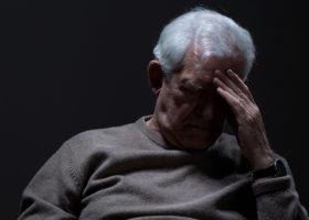 Äldre vithårig man med handen på pannan