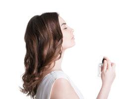 Blundande kvinna sprayar parfym på halsen