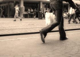Kvinna bär vit plastpåse på gata, svartvit bild