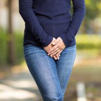 Kvinna i jeans håller handen för skötet som om kissnödig