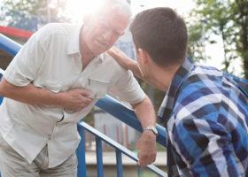 Äldre man håller sig för hjärtat och ung man kommer till undsättning