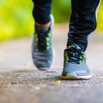 Fötter i gymnastikskor promenerar på stig