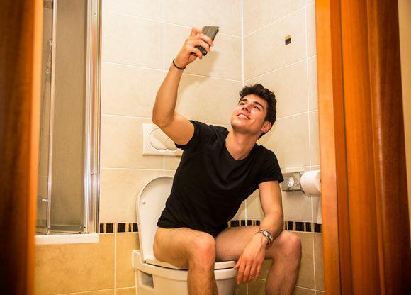Ung kille sitter på toalett och tar en selfie